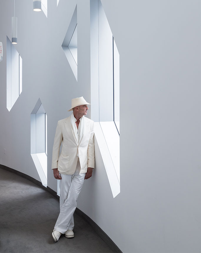 Alan Faena leaning against wall
