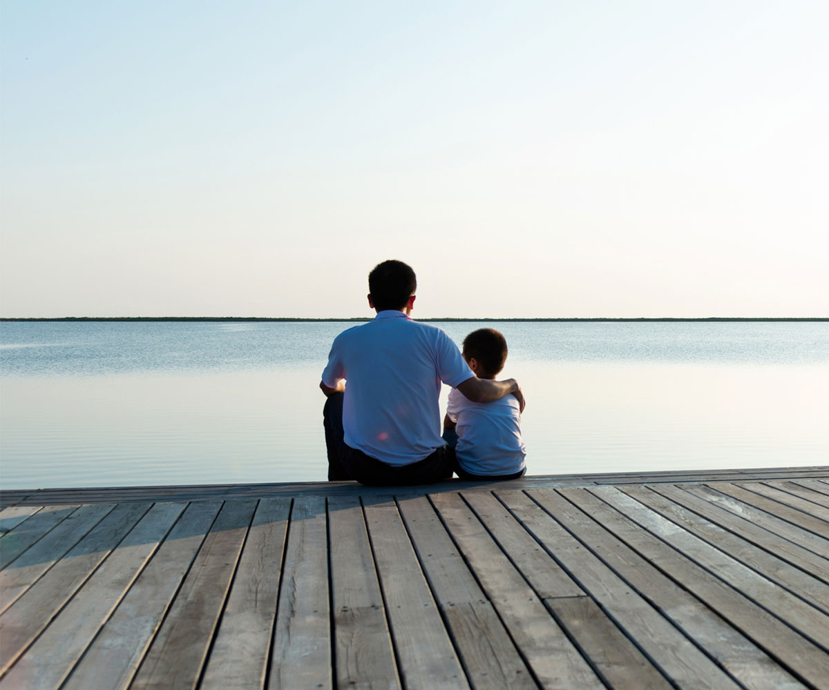 Father with his son enjoying lake view