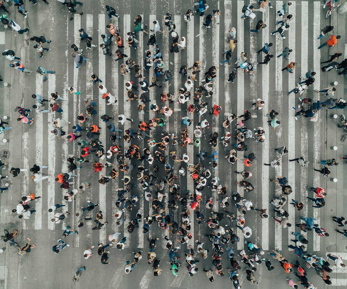 Aerial view of large crowd crossing road in Latin America