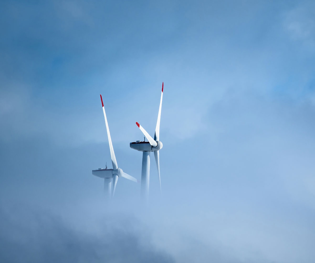 Wind turbines appearing over clouds