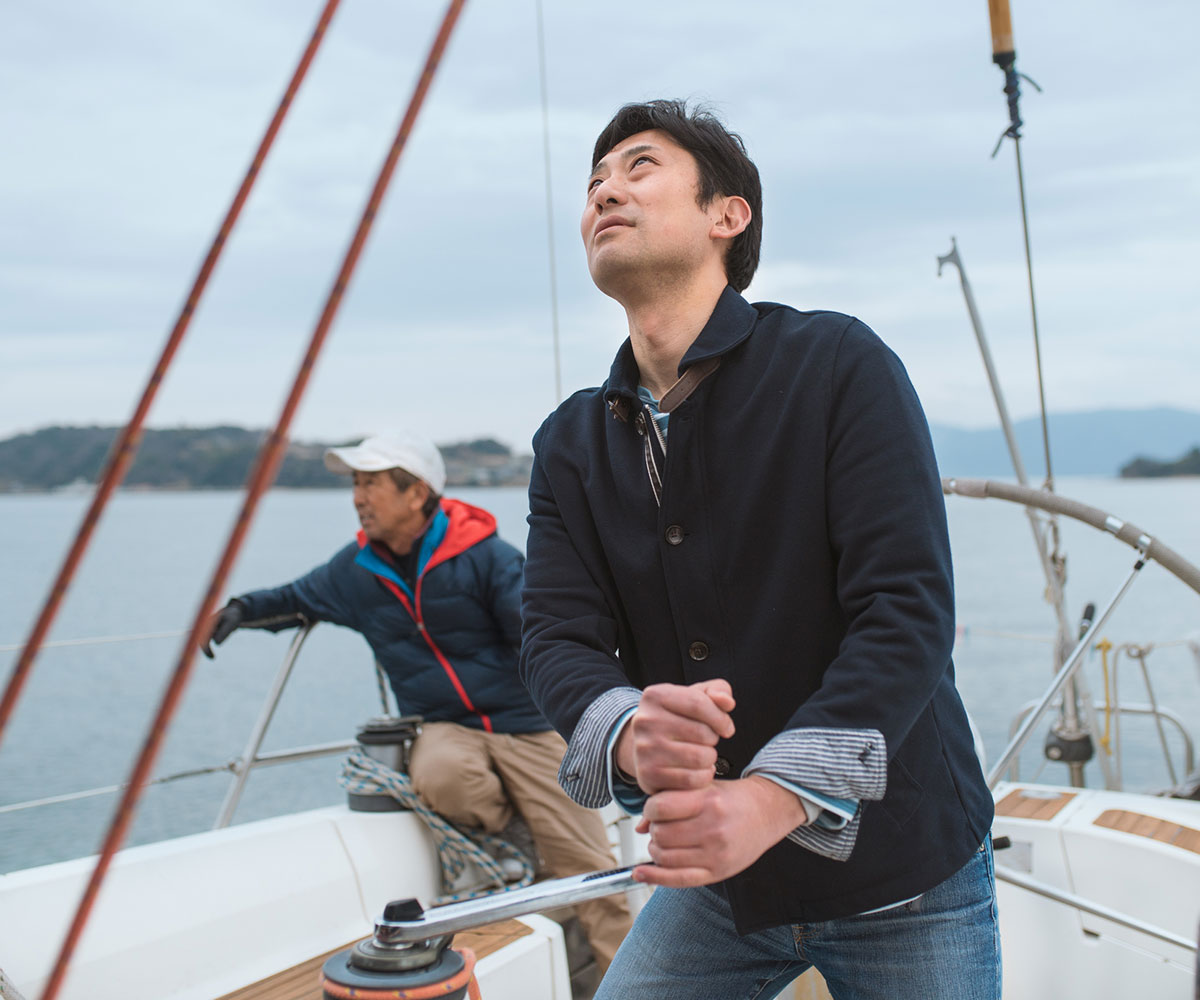 Father and son together on a luxury yacht. The son is hoisting the sail whilst the father relaxes. Okayama, Japan.