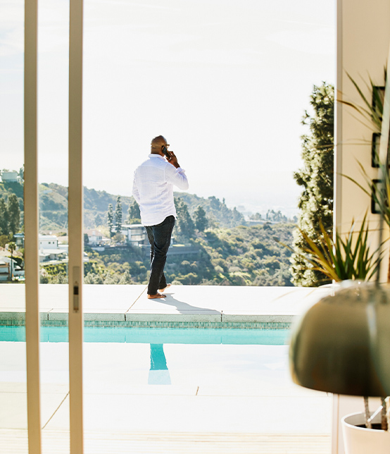 Man on the phone standing in front of a swimming pool and mountains